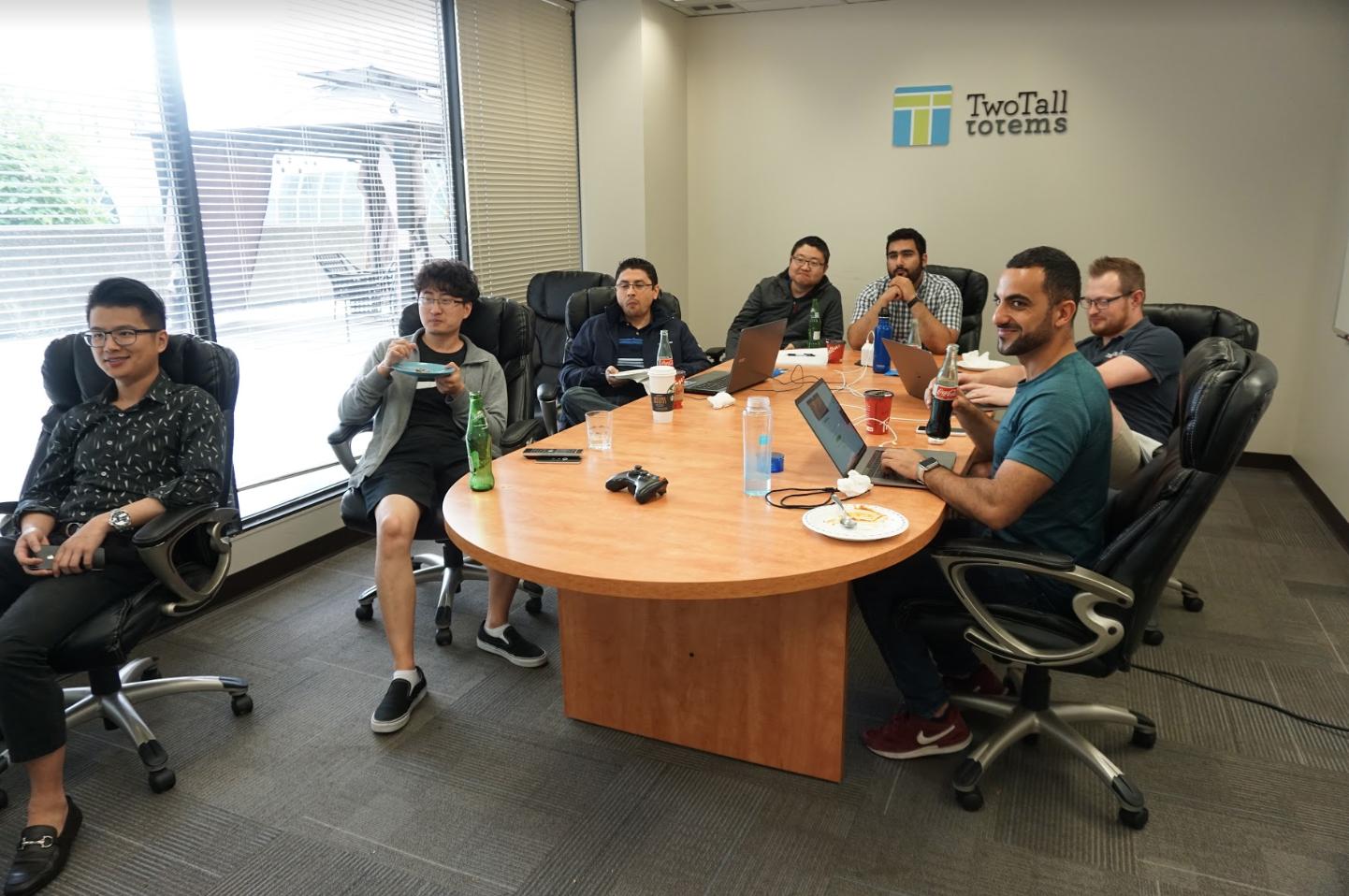 TTT team watching hackathon presentation in boardroom