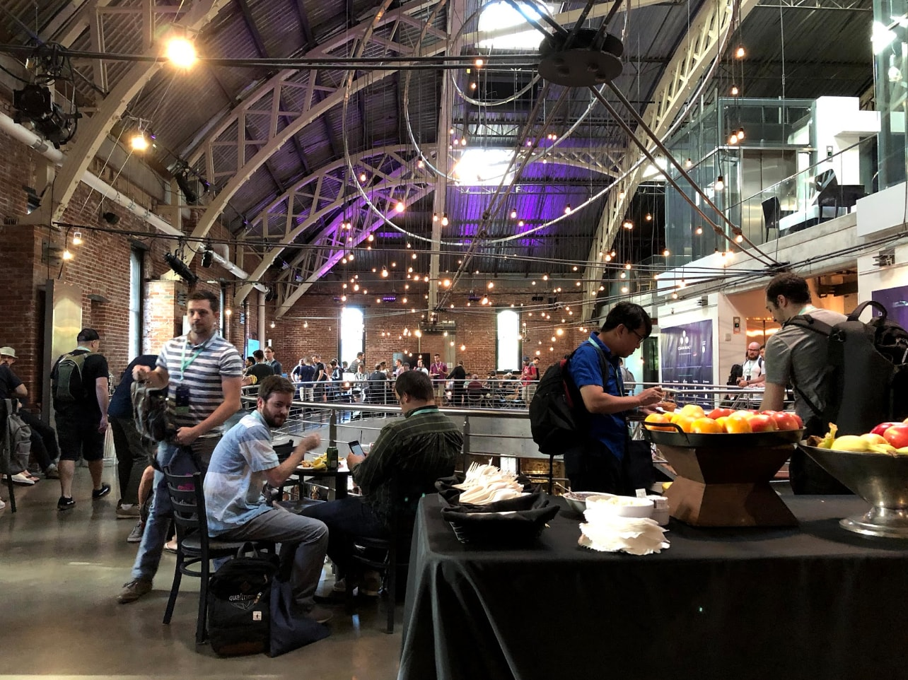Developers mingling and snacking at the React Native Conference