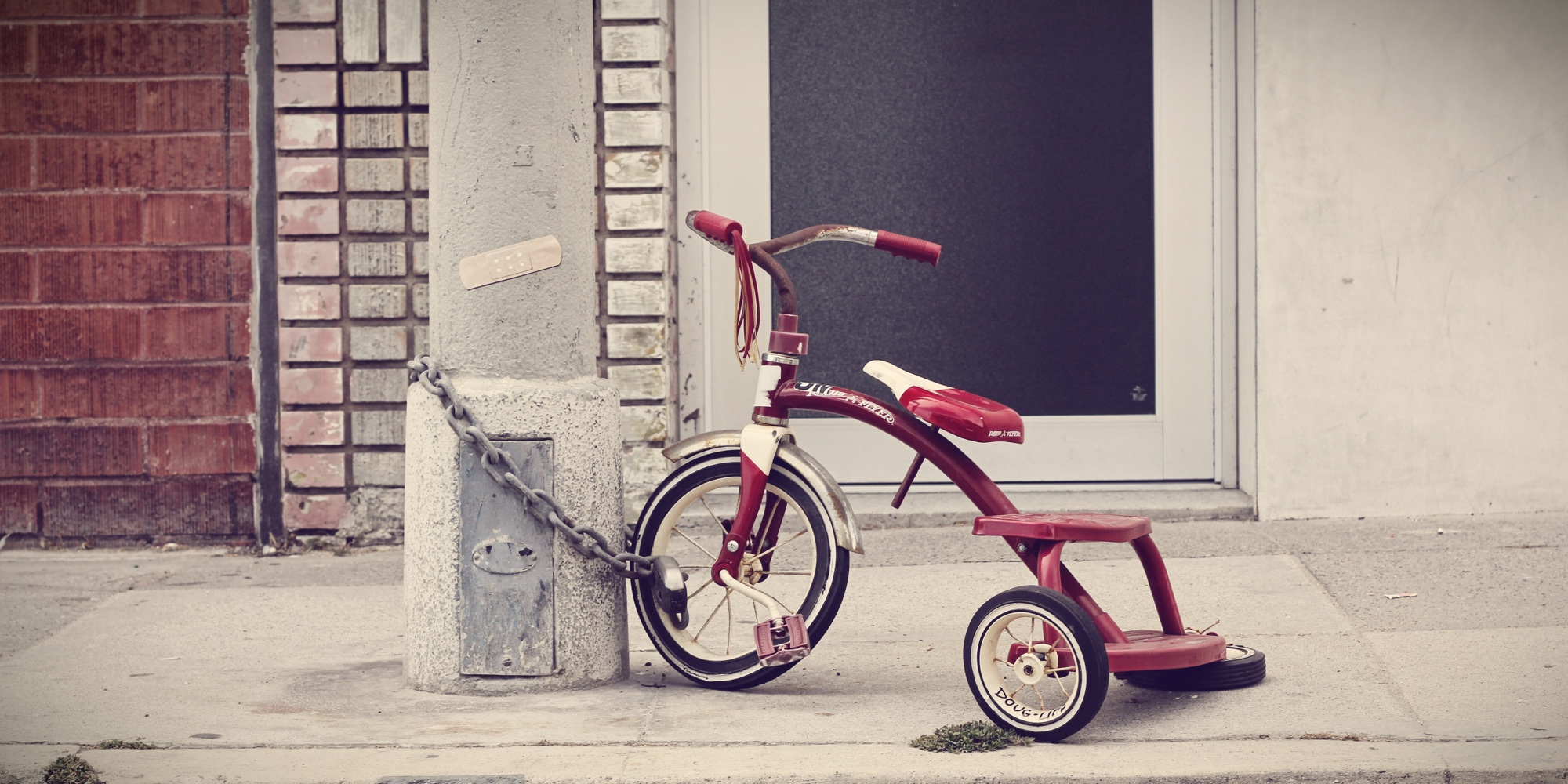 The hypocrisy of parental controls blog banner of a tricycle chained to a post