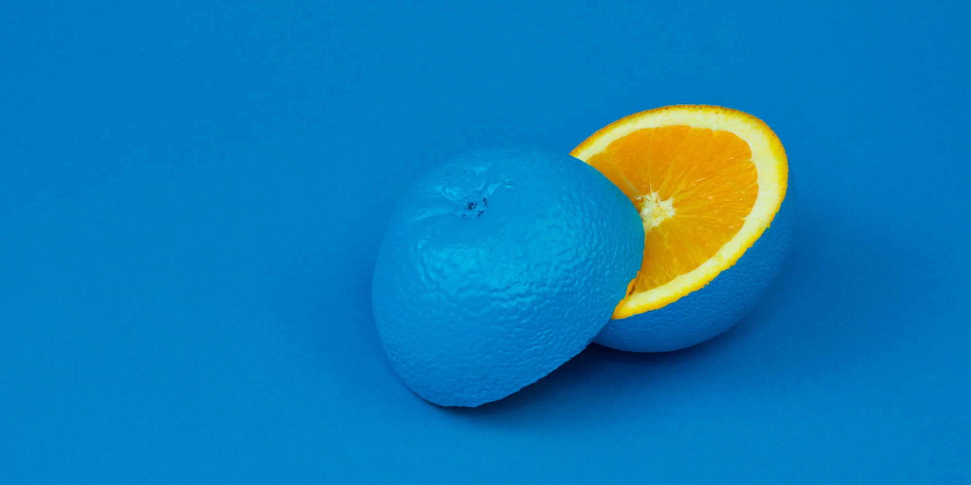Picture of a orange painted blue cut open showing the orange in the middle