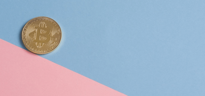 Picture of a colour blocked background with one physical bitcoin coin