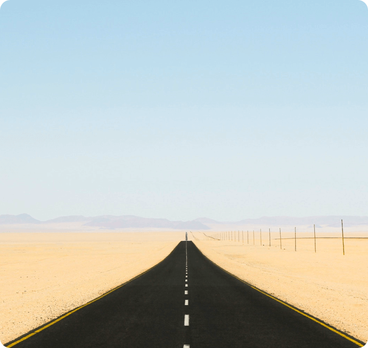 Picture of a straight road leading towards the mountains in the middle of a flat landscape