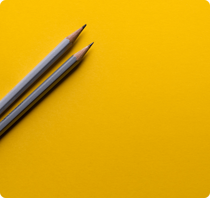 Yellow background with two sharpened pencils