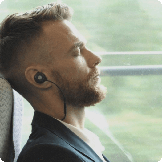 Man sitting on train with Revols earphones device in his ear