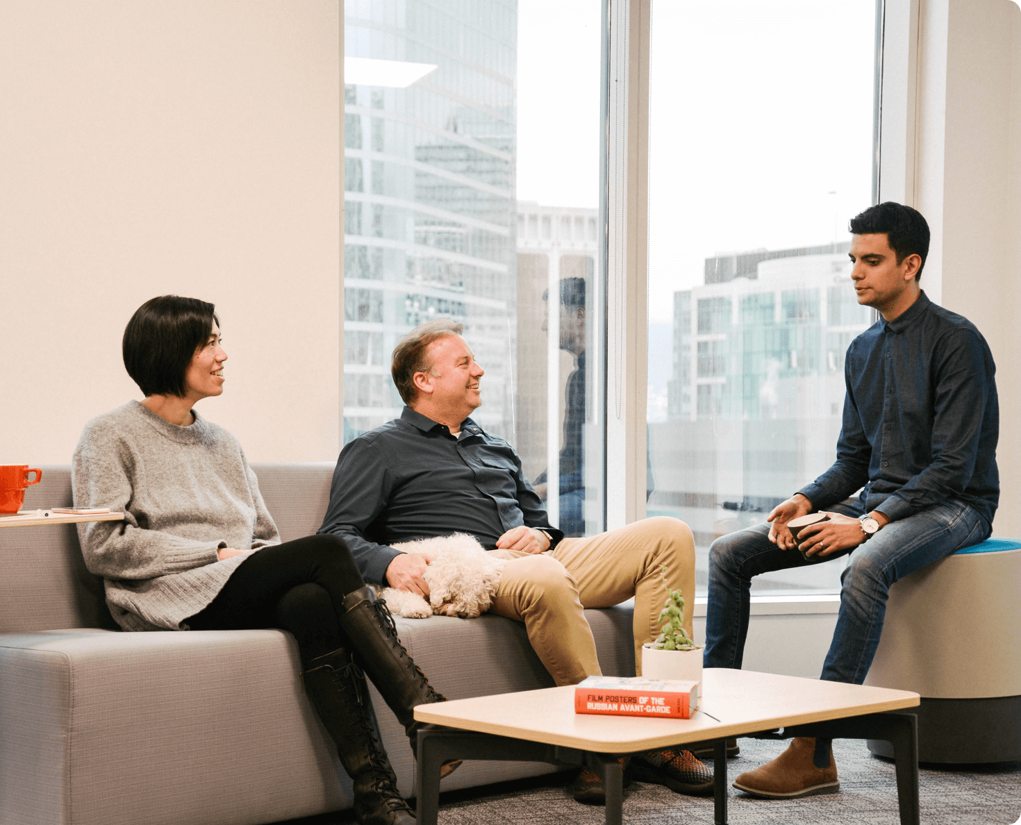Picture of three people casually having a conversation on a couch