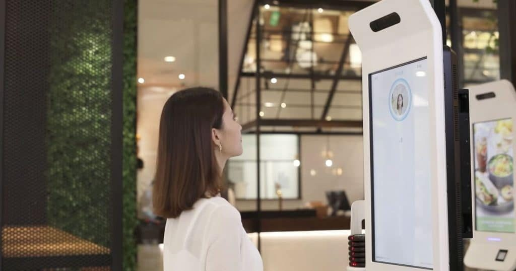 Person using facial recognition software to pay for meal at KFC kiosk