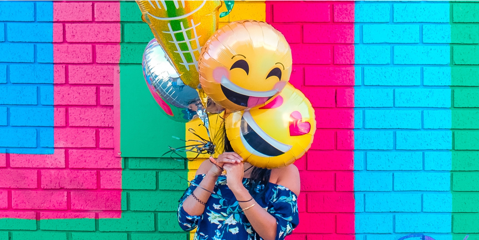 Colourful image of person holding emoji balloons.