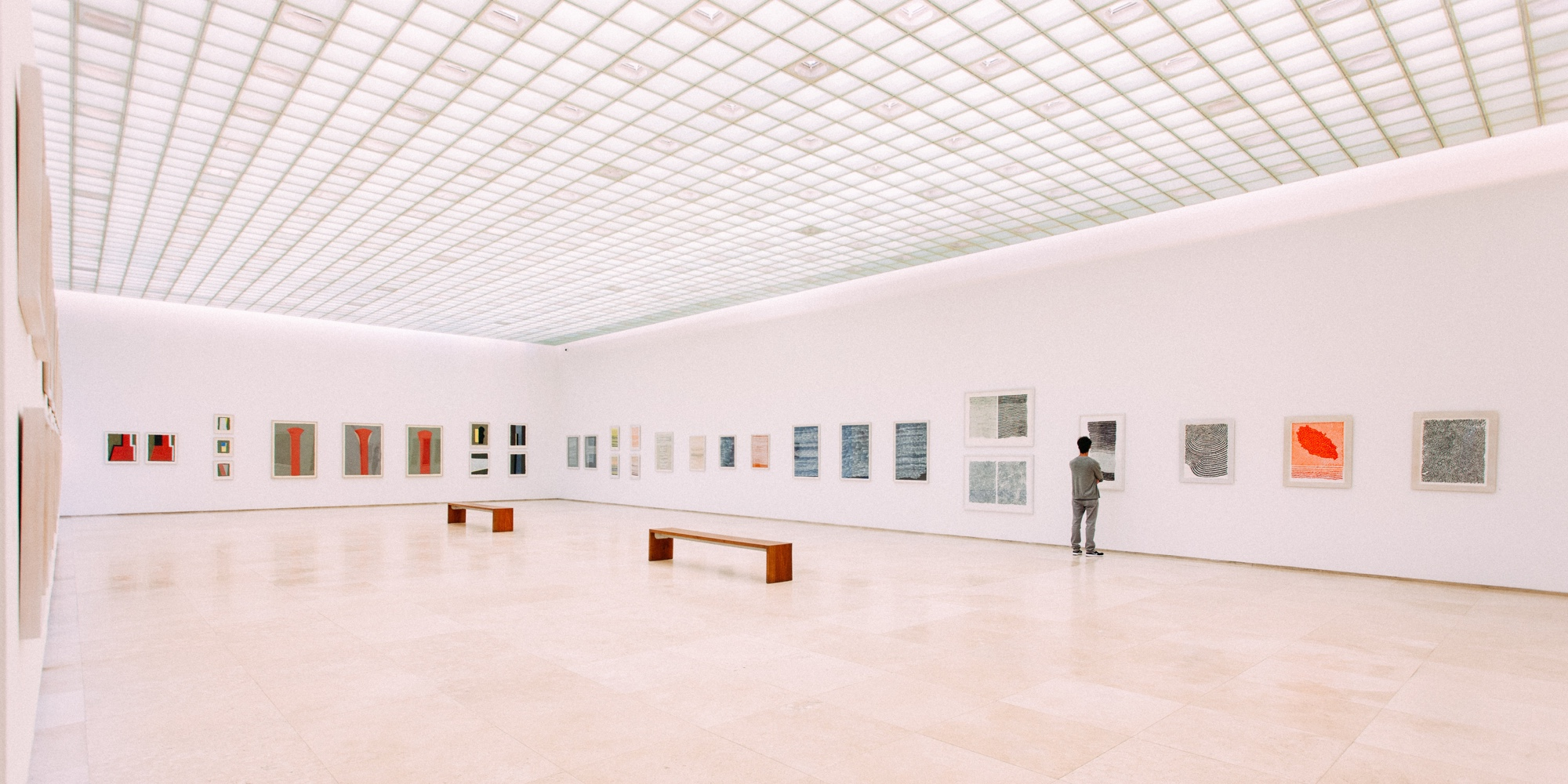 Banner showing man looking at paintings in a museum for website marketing blog.