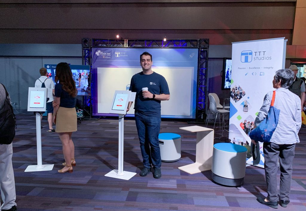 Photo of TTT's business development manager, Amer, posing beside a facial recognition check-in kiosk