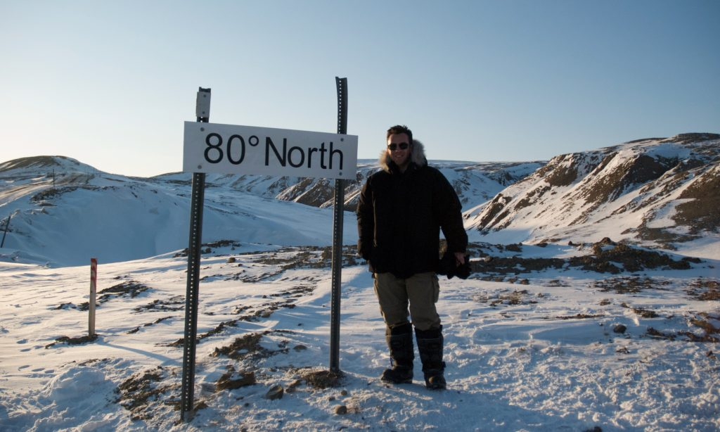 Project manager Nick W posing beside sign in the arctic