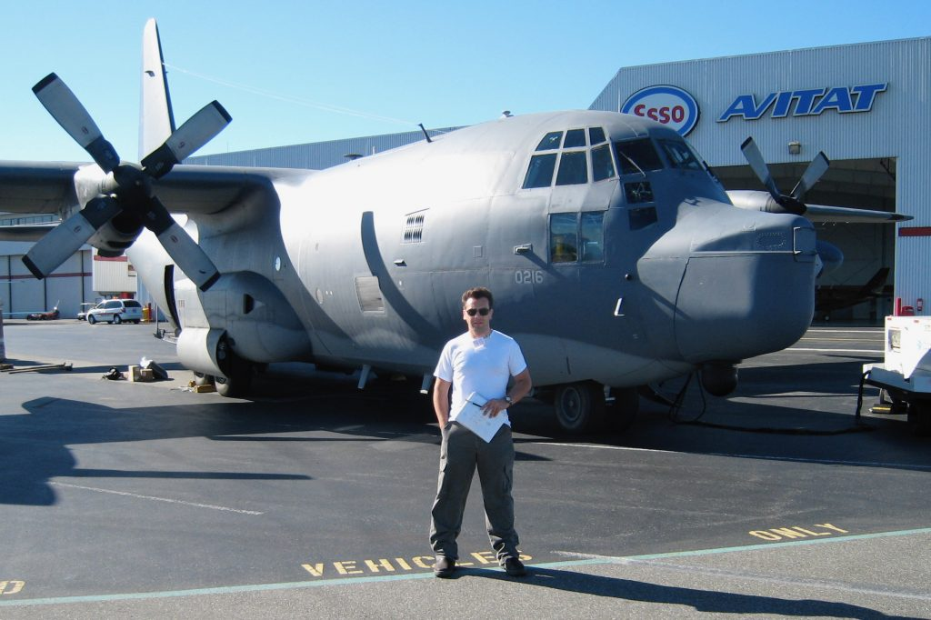 Project manager Nick W standing beside MC-130 Hercules plane