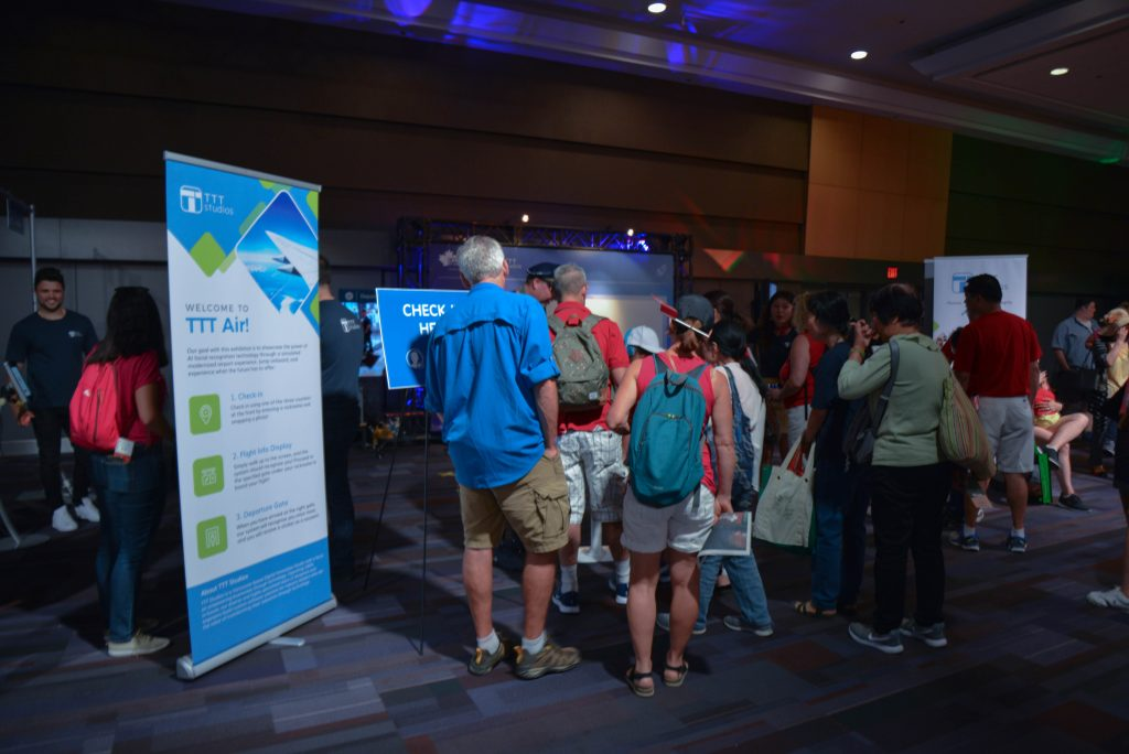 Crowd of people enjoying TTT's Canada Day facial recognition airport boarding simulation exhibit