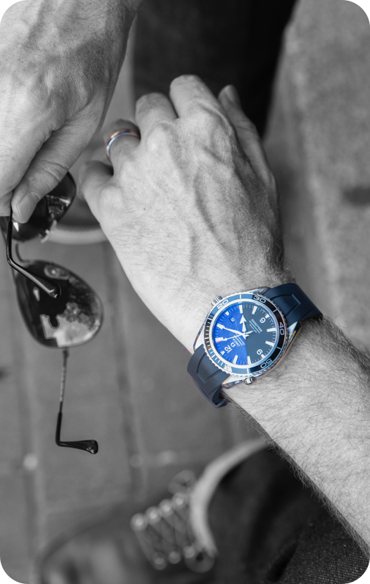 black and white picture with blue luxury watch on wrist