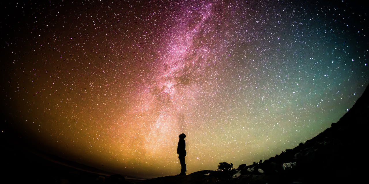 A person looking up at a starry and colourful night sky