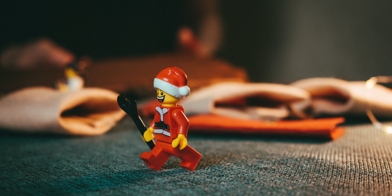 A Santa Lego guy holds a wrench and is walking