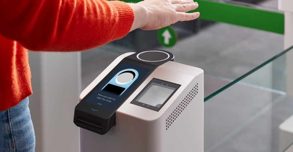 A person waving their hand over a palm scanner for payment.