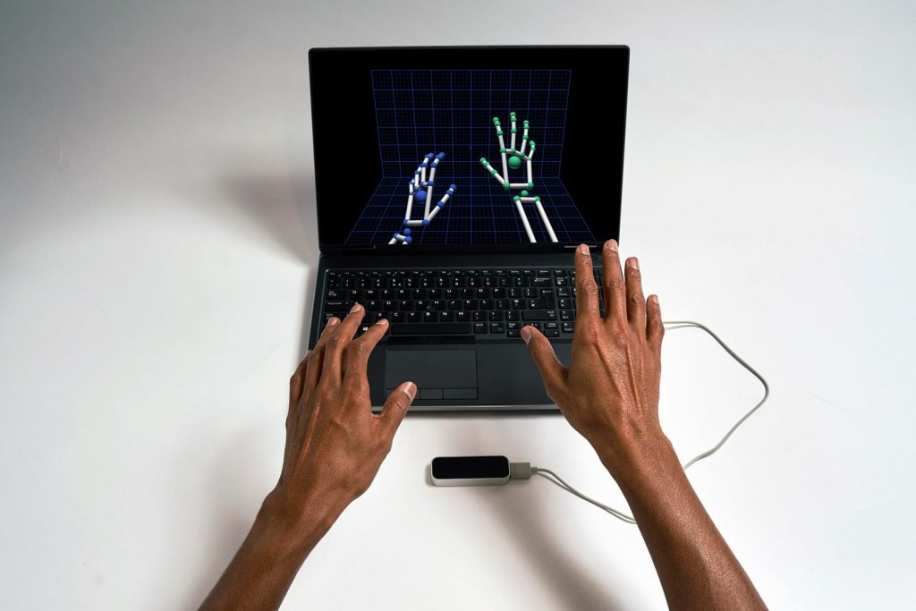 An individual hovering their hands over the Leapmotion controller and their hands are shown on a screen.