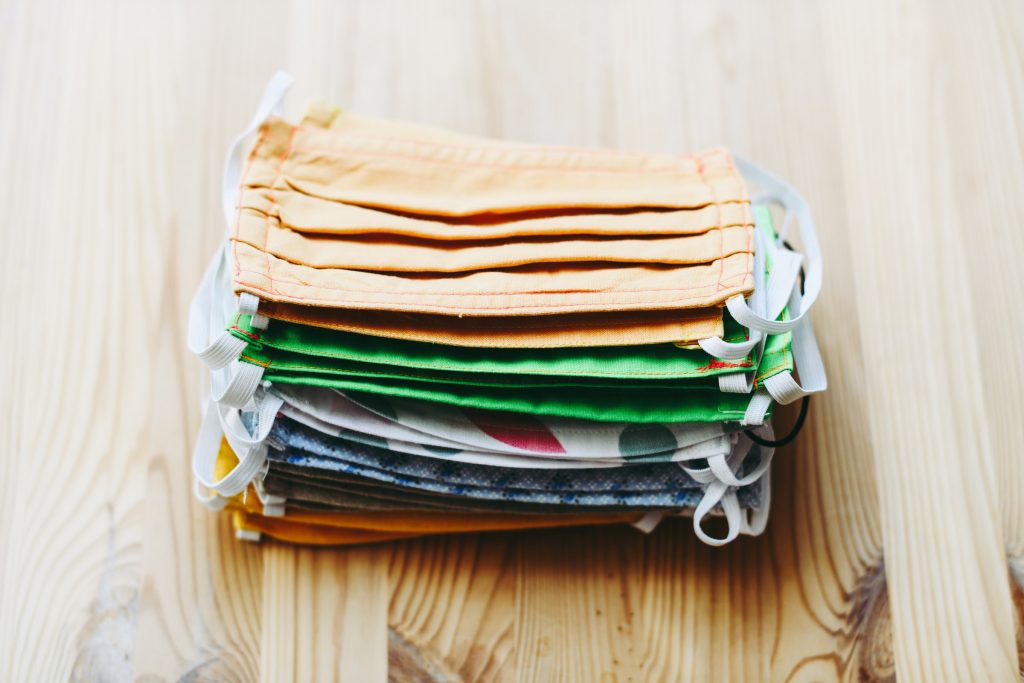 A pile of face masks on a wooden table.