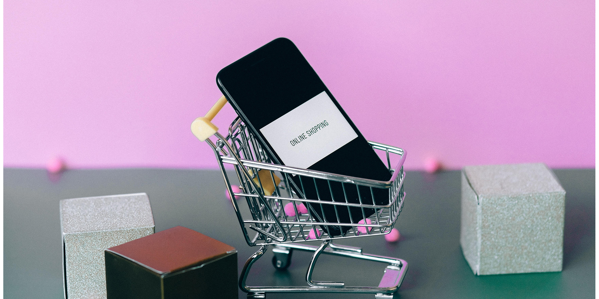 """Phone showing the phrase """"online shopping"""" in a small shopping cart"""